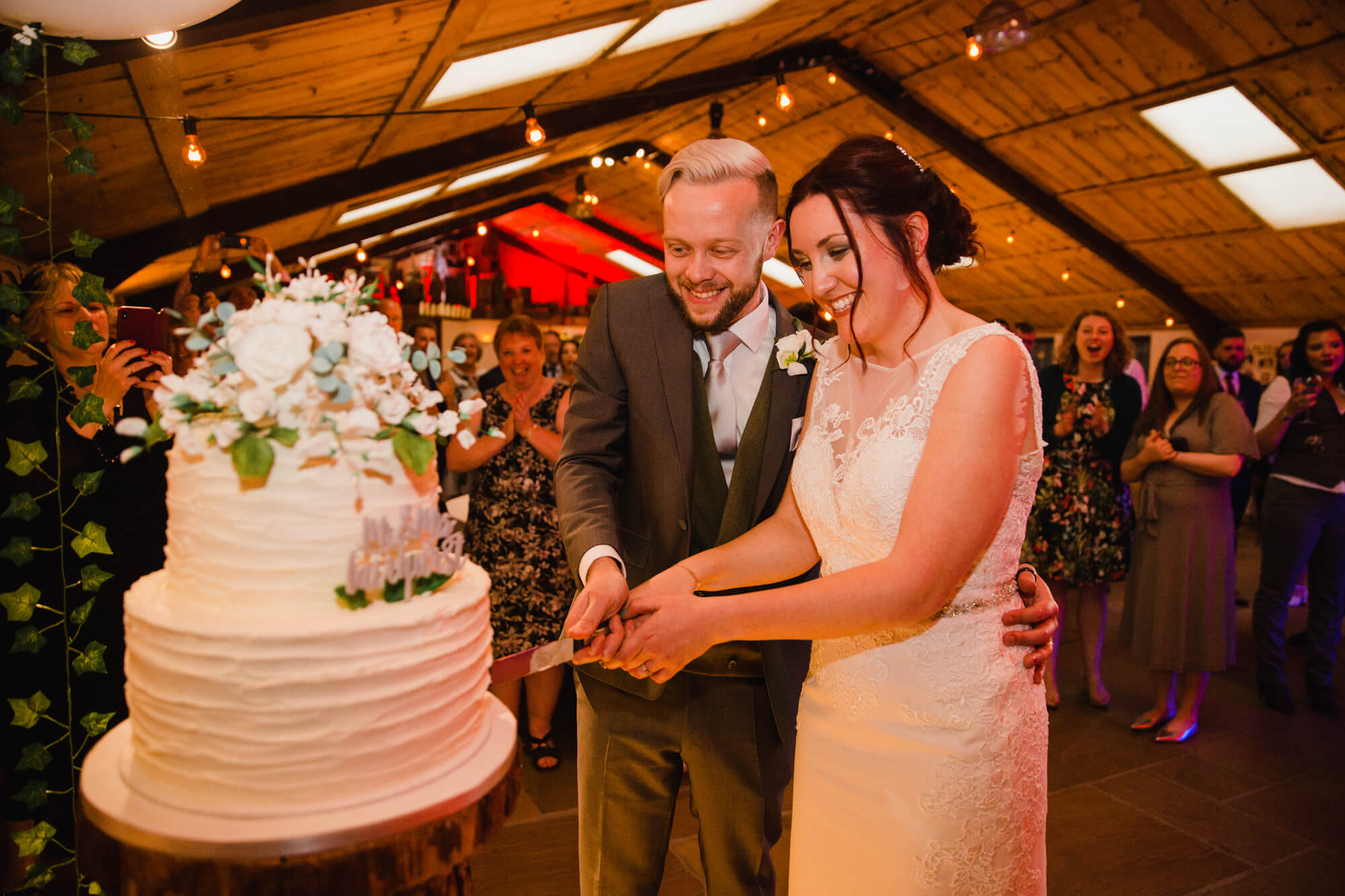 newly married couple cutting into wedding cake surrounded by family and friends