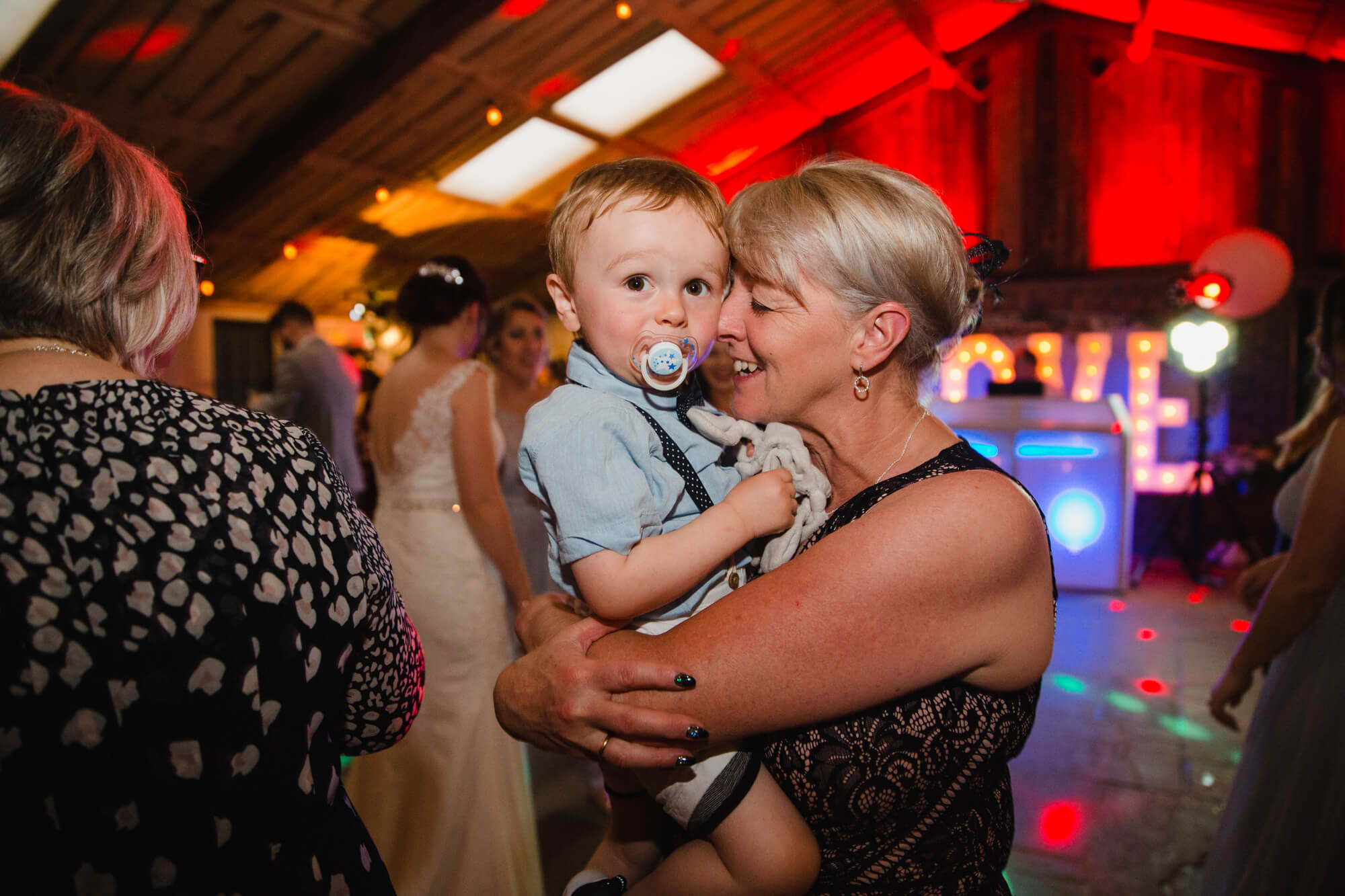 page boy being held on dance floor for intimate photograph looking into camera