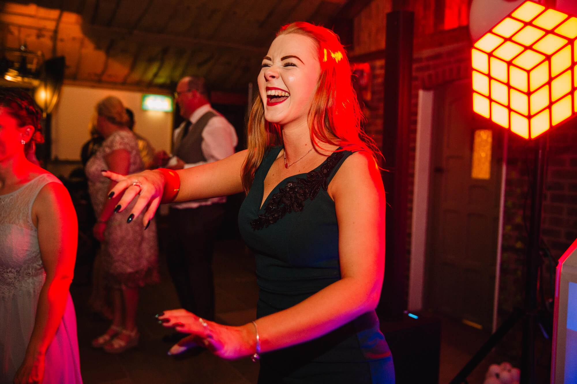 maid of honour dancing and laughing at end of evening in a high contrast colourful photograph