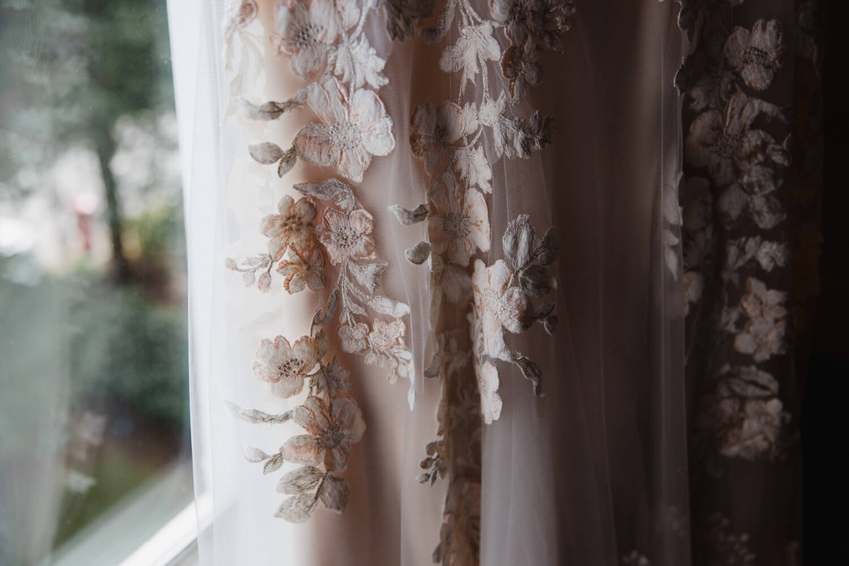 close up macro lens photograph of wedding dress detail in window light