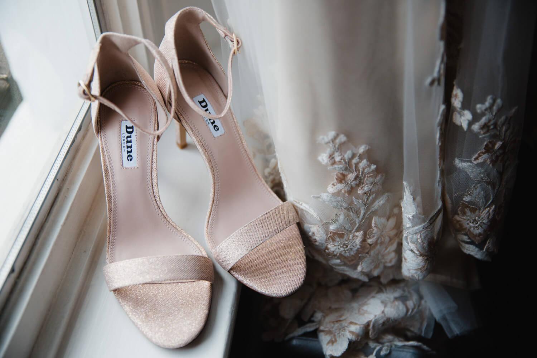bridal wedding shoes on window alongside bridal gown