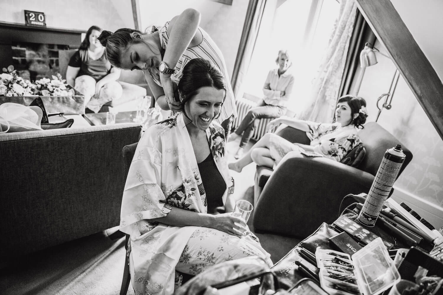 black and white photograph of bride having hair styled