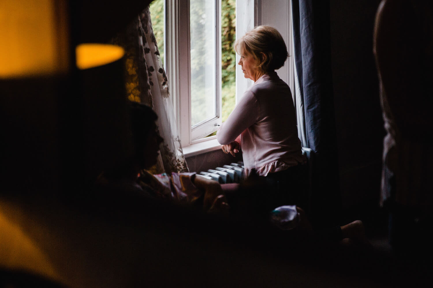 low light exposure photograph of mother looking out window