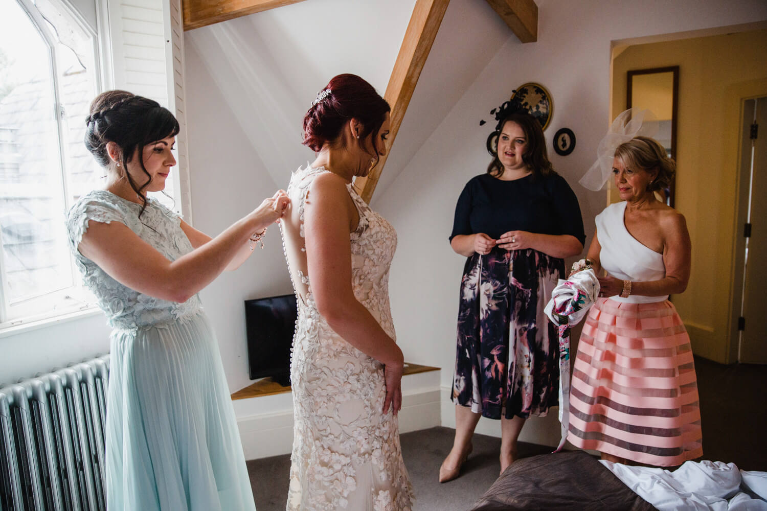 bridesmaid fastens buttons on back of brides dress while bridal party look on