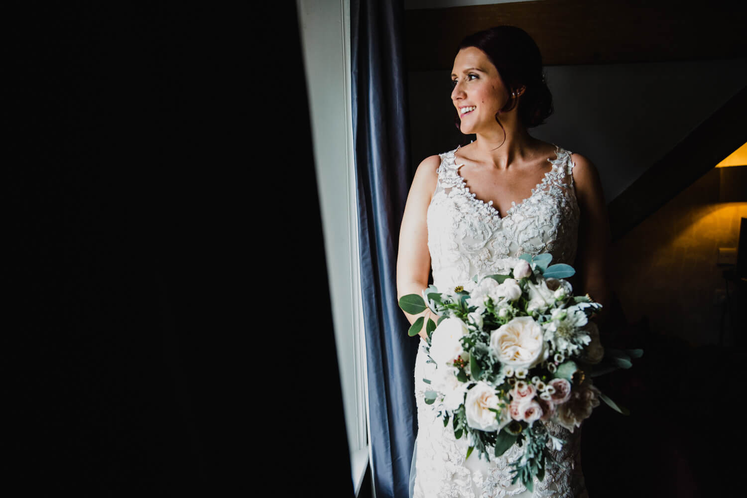 wedding portrait of bride looking out from window at eleven didsbury park