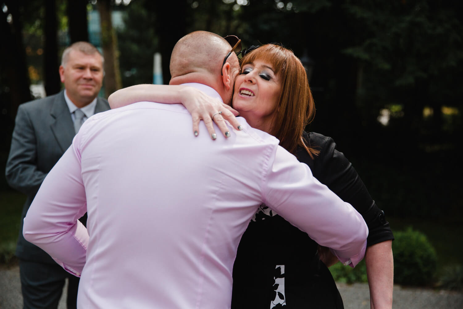 maid of honour sharing hug with groom before wedding service