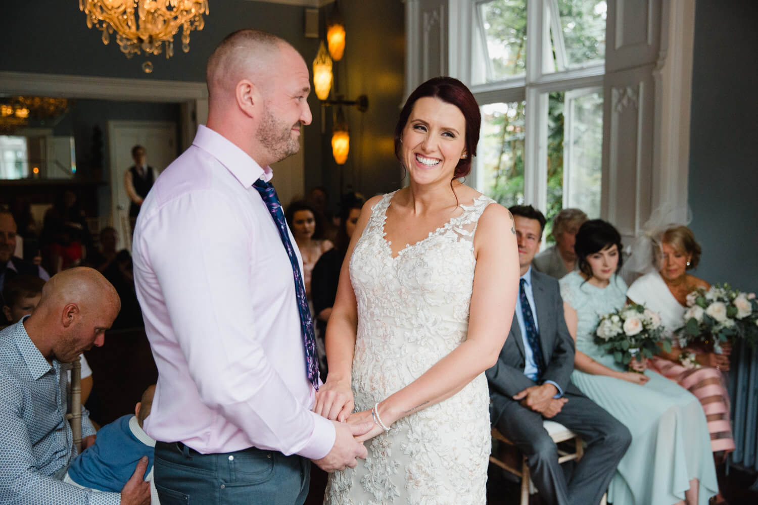 bride laughing and smiling during ceremony while groom looks on