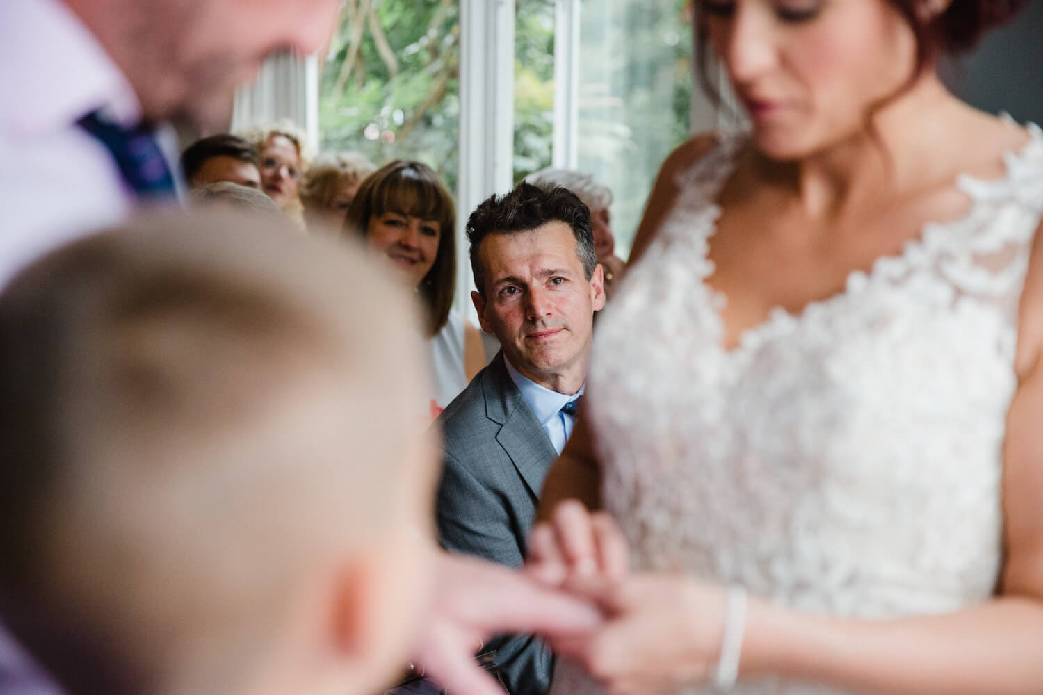 close up intimate photograph of father looking on while bride and groom exchange wedding rings