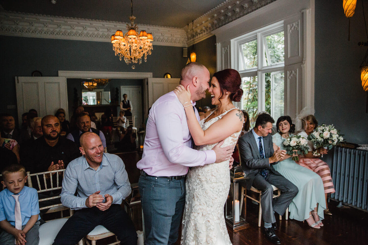 wide angle photograph of eleven Didsbury park wedding as family and friends applaud