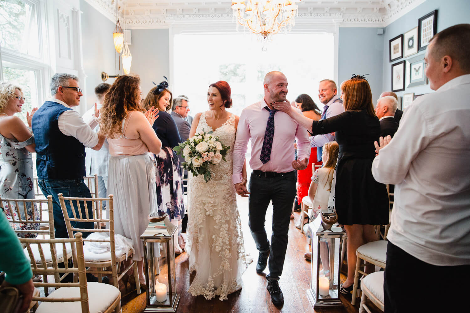 newly married couple walk down aisle for ceremony processional and congratulated by wedding party