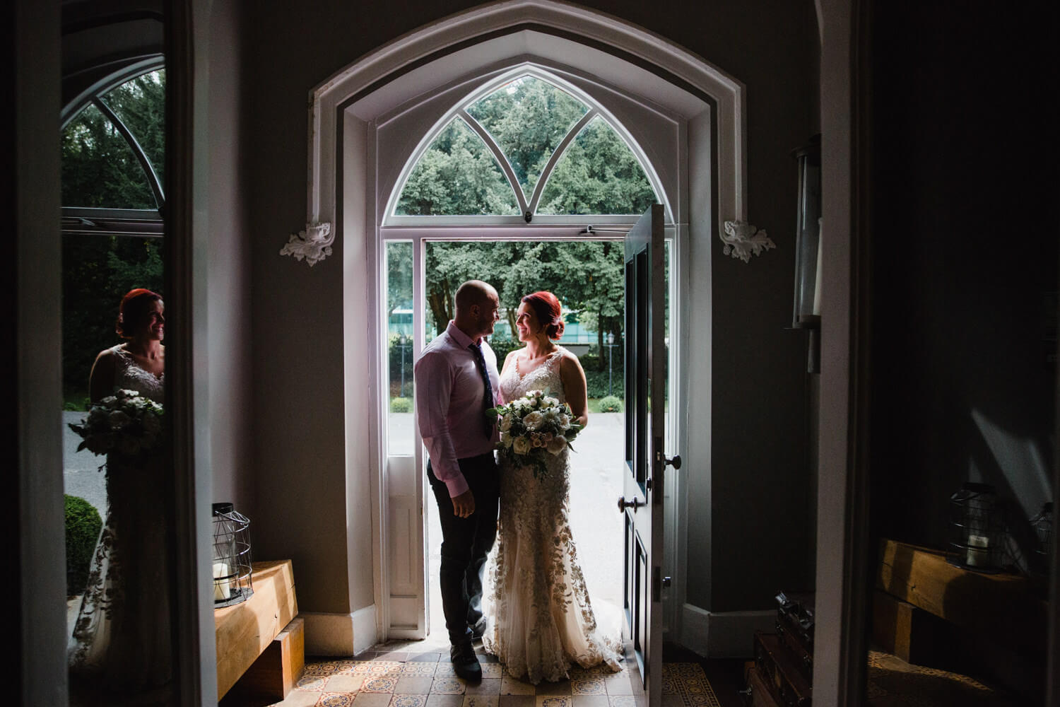 low light exposure photograph of newlywed couple stood in doorway holding bouquet of flowers