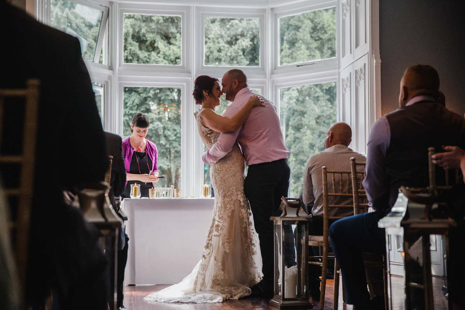 photograph from back of ceremony showing newlyweds kissing in window at Eleven Didsbury Park