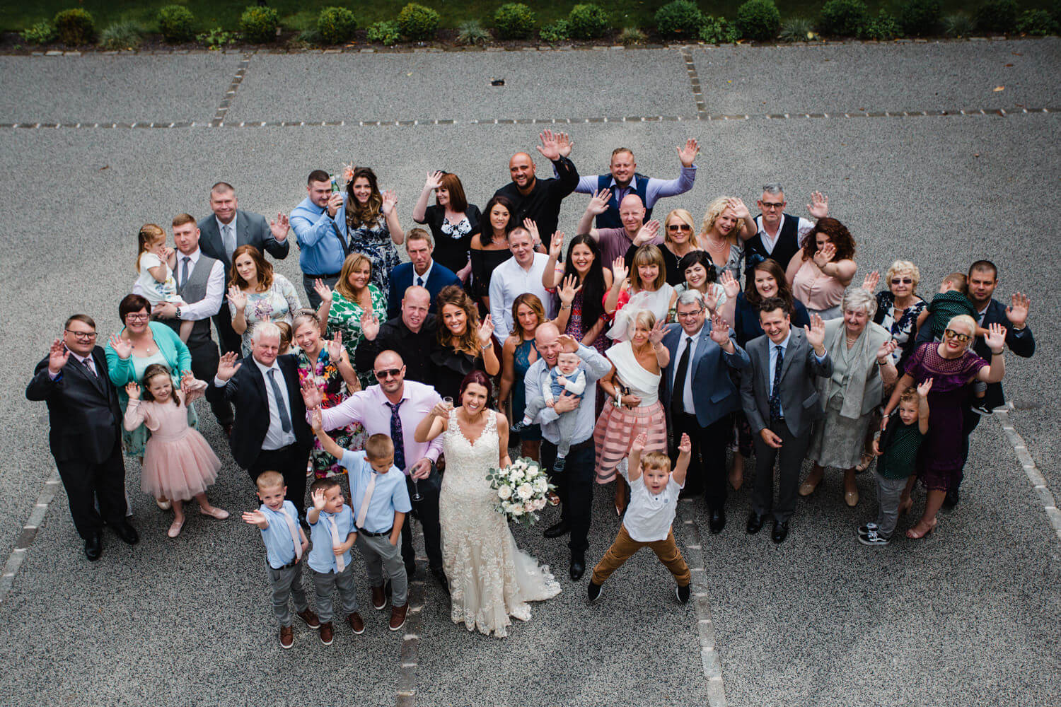 wide angle lens photograph of wedding party group photograph outside eleven didsbury park