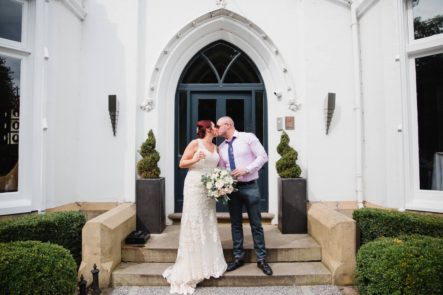 Newly married couple kissing on steps of eleven Didsbury house