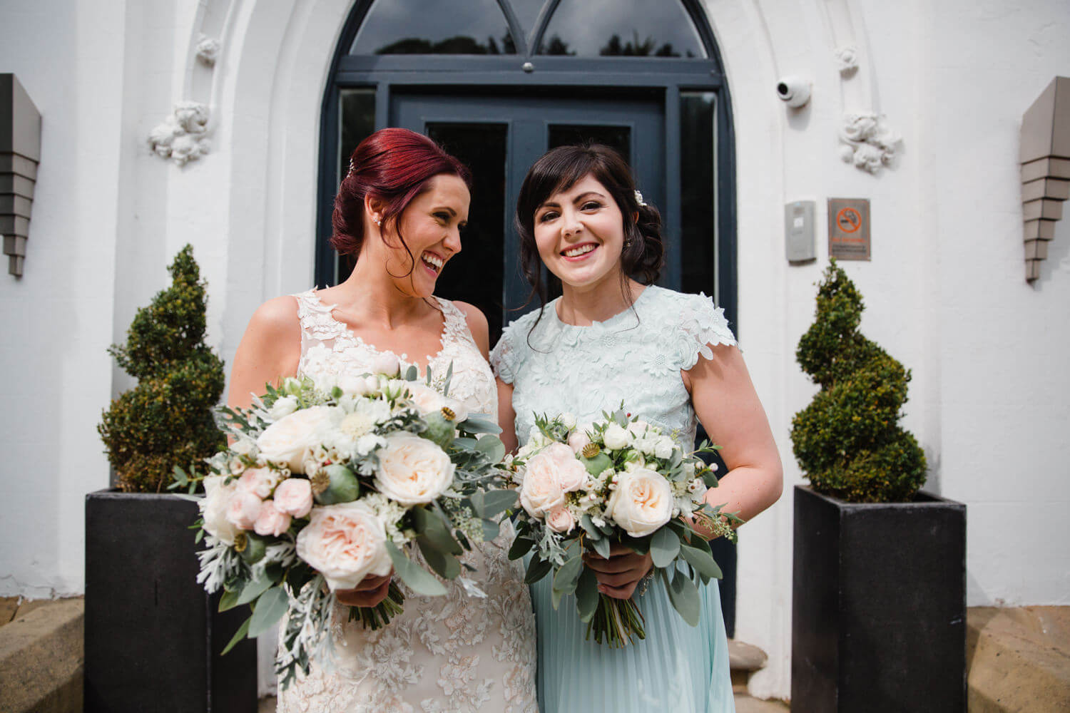 bride sharing moment with bridesmaid sister while holding floral bouquets