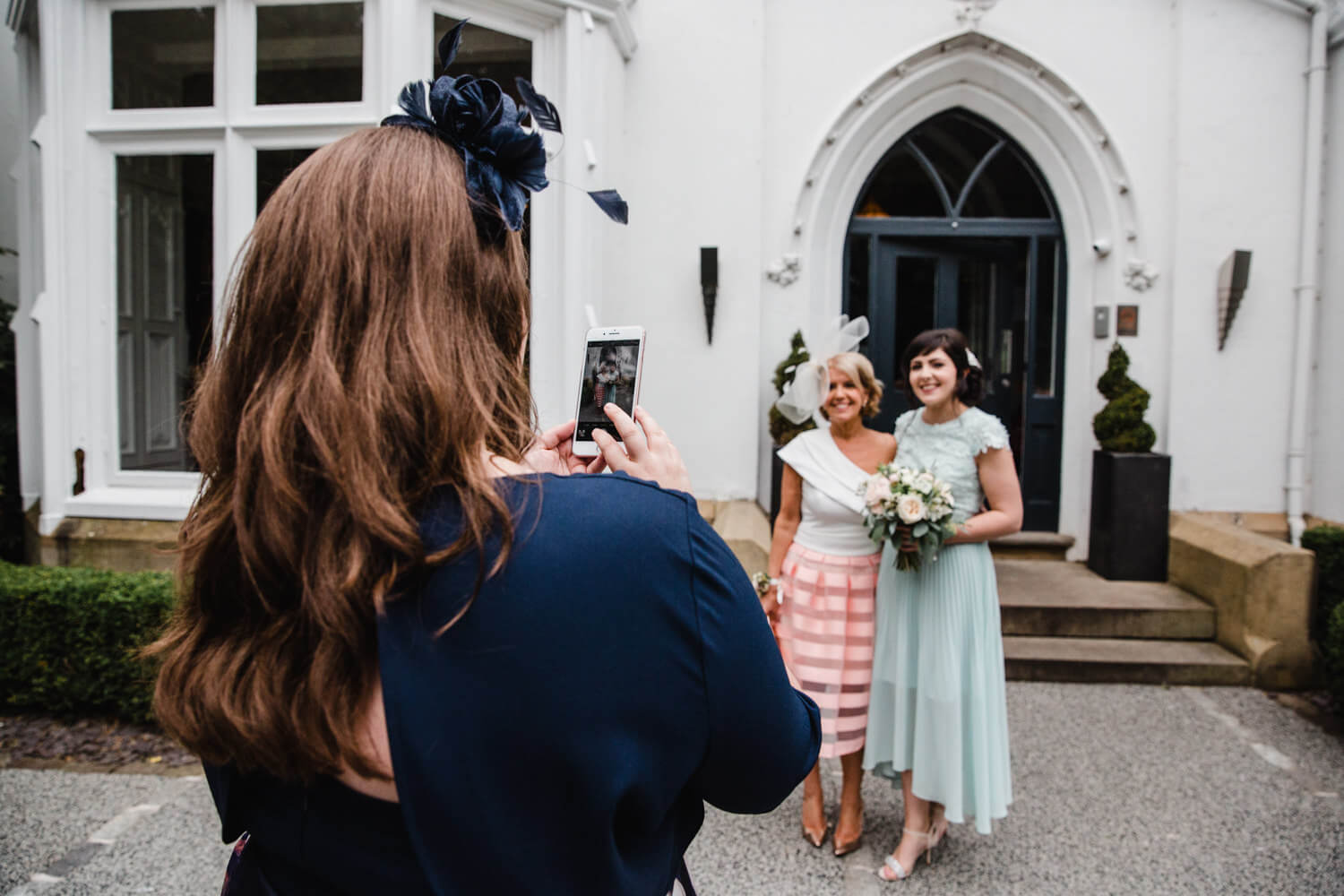 bridesmaid taking camera phone photograph of bridal party in front of Eleven Didsbury House