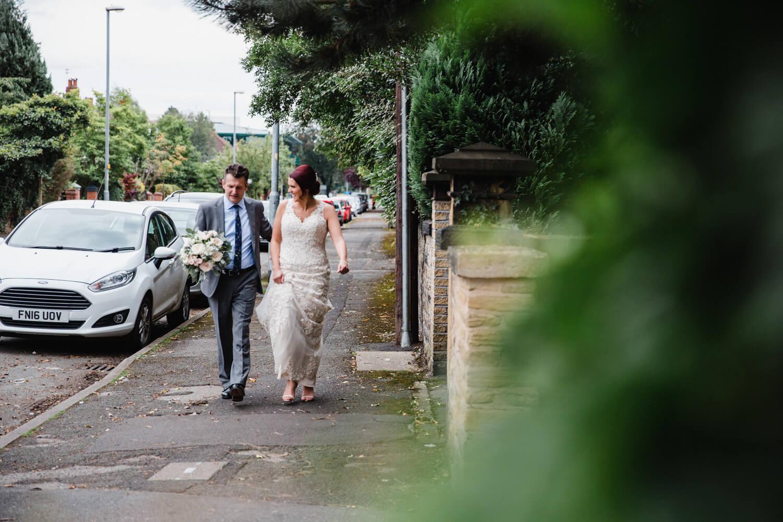 bride and father walking down Didsbury road to reception venue