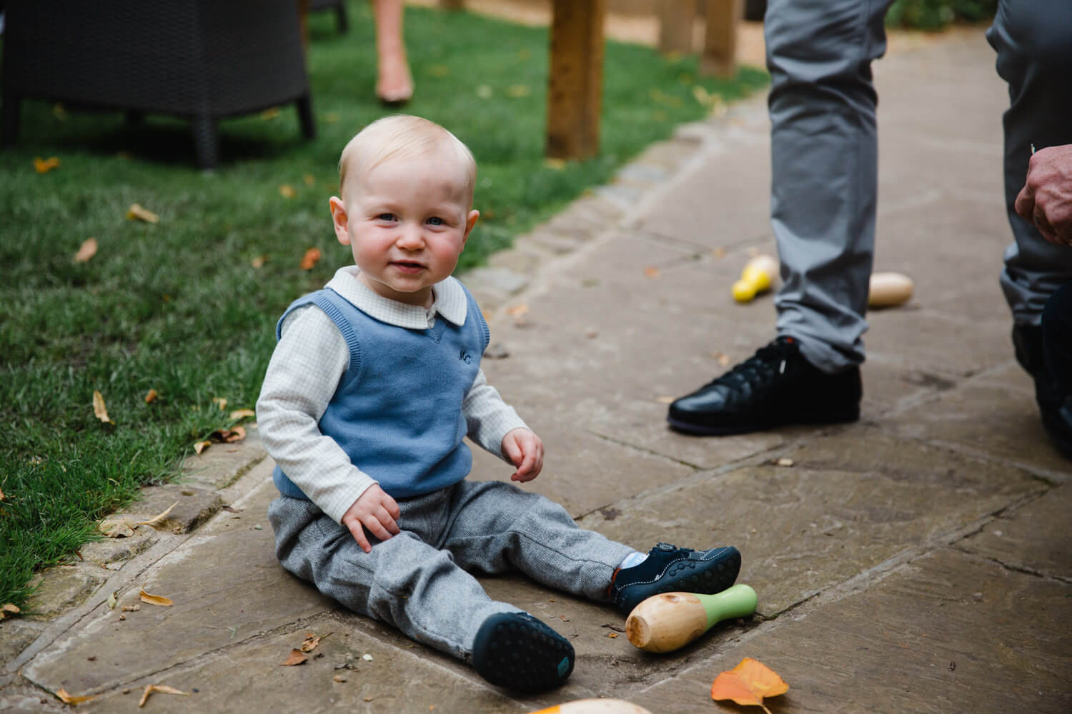 page boy sat on floor looking at camera while playing skittles lawn game
