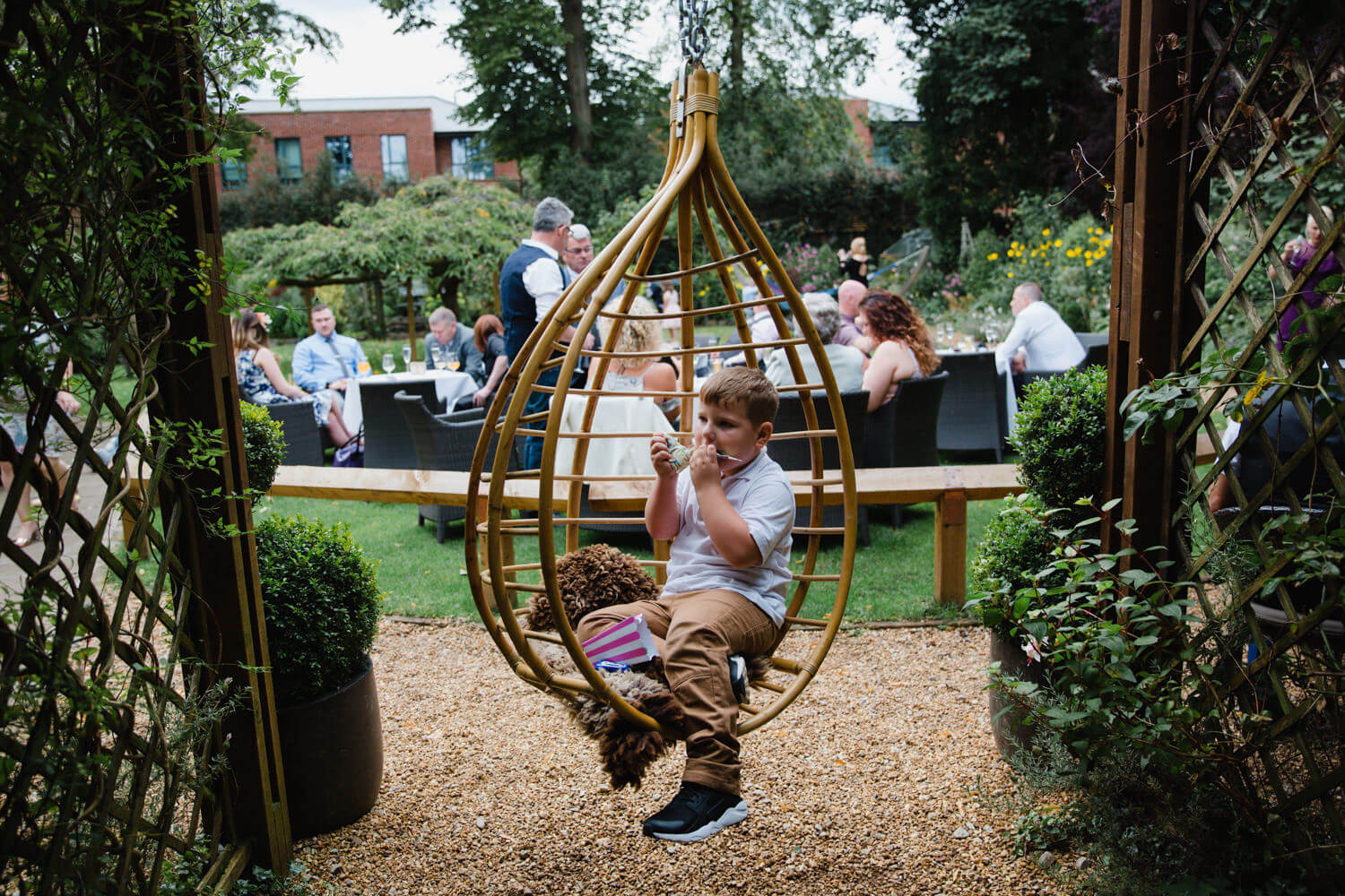 page boy sat in garden swing eating with wedding party sat behind