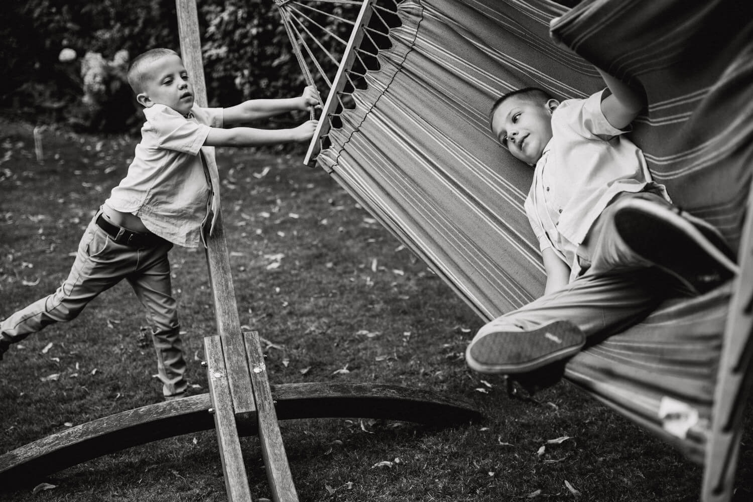 black and white photograph of page boys playing with hammock during drinks reception