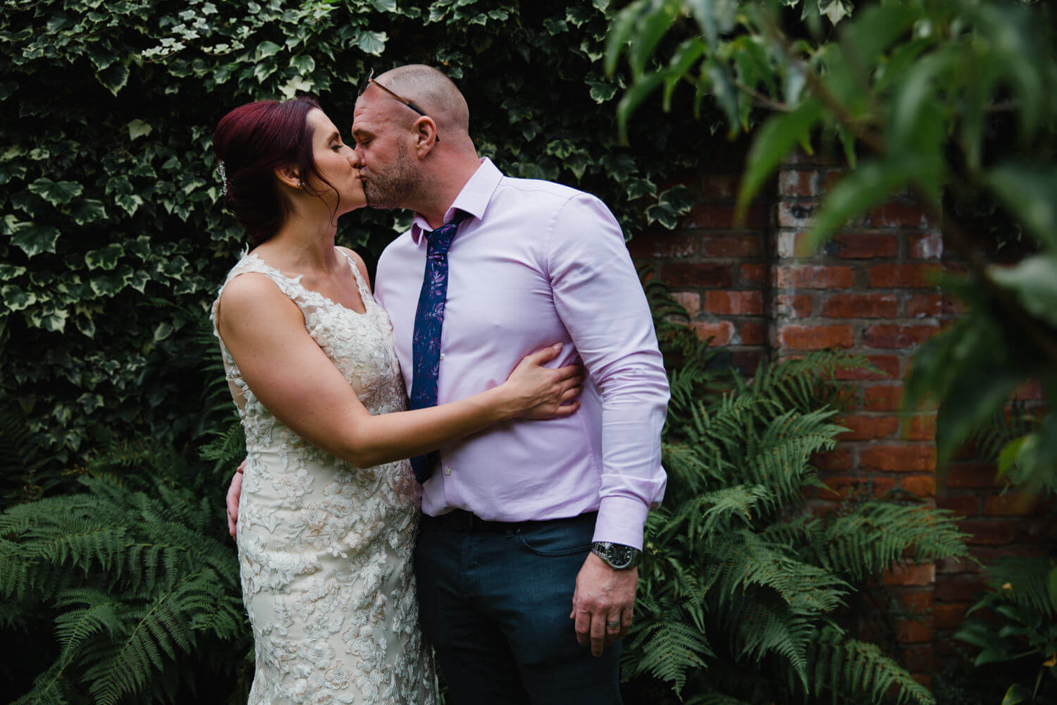 landscape portrait of bride and groom kissing in gardens of Eleven Didsbury Park