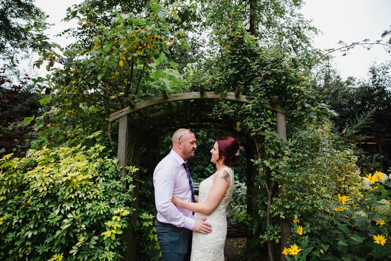 newlyweds posing in garden archway of Eleven Didsbury Park