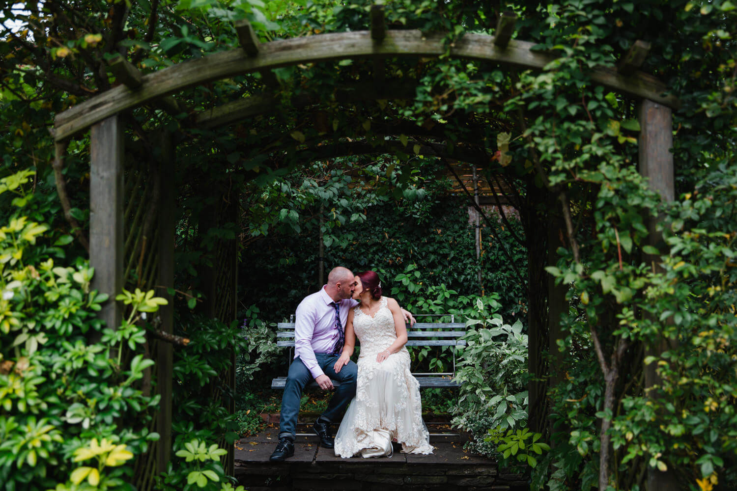 intimate kiss by the newly married couple in grounds of Eleven Didsbury Park