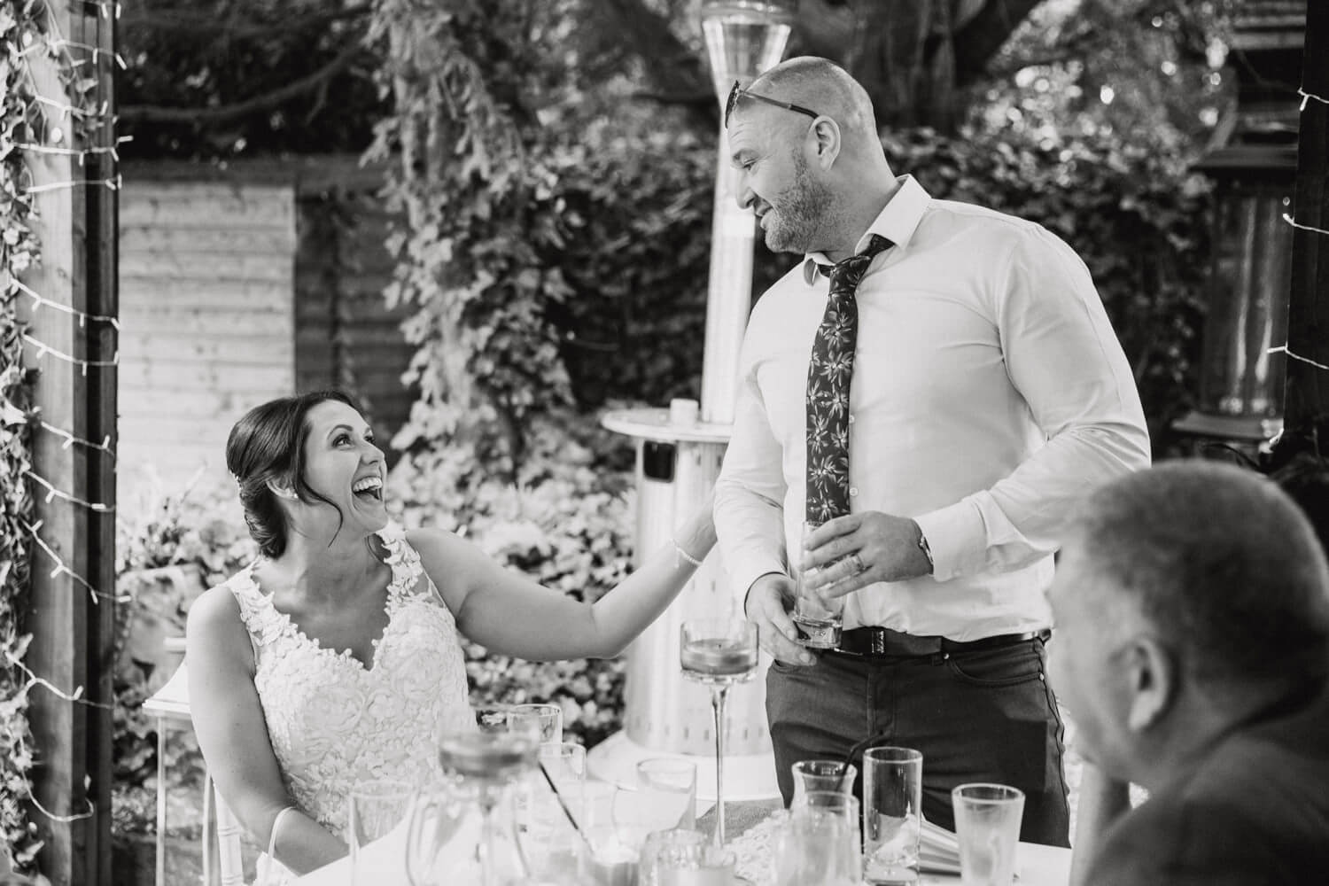 black and white photograph of bride laughing at grooms speech at Eleven Didsbury Park