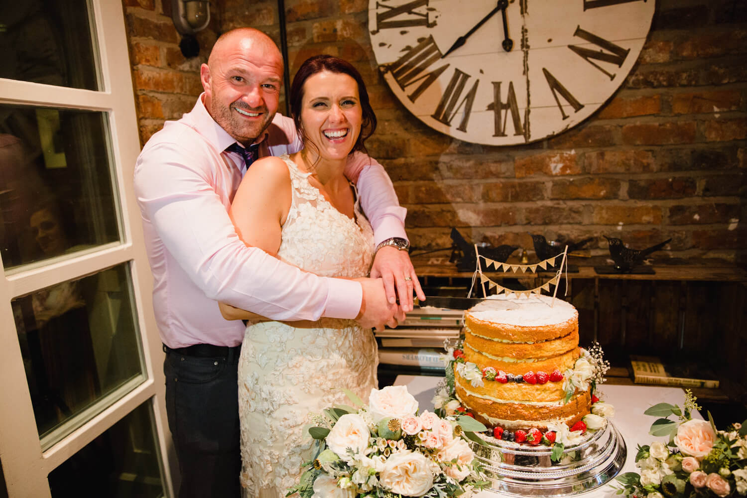 bride and groom cutting cake together at Eleven Didsbury Park