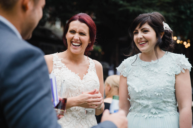 bride and bridesmaid talking to wedding guests