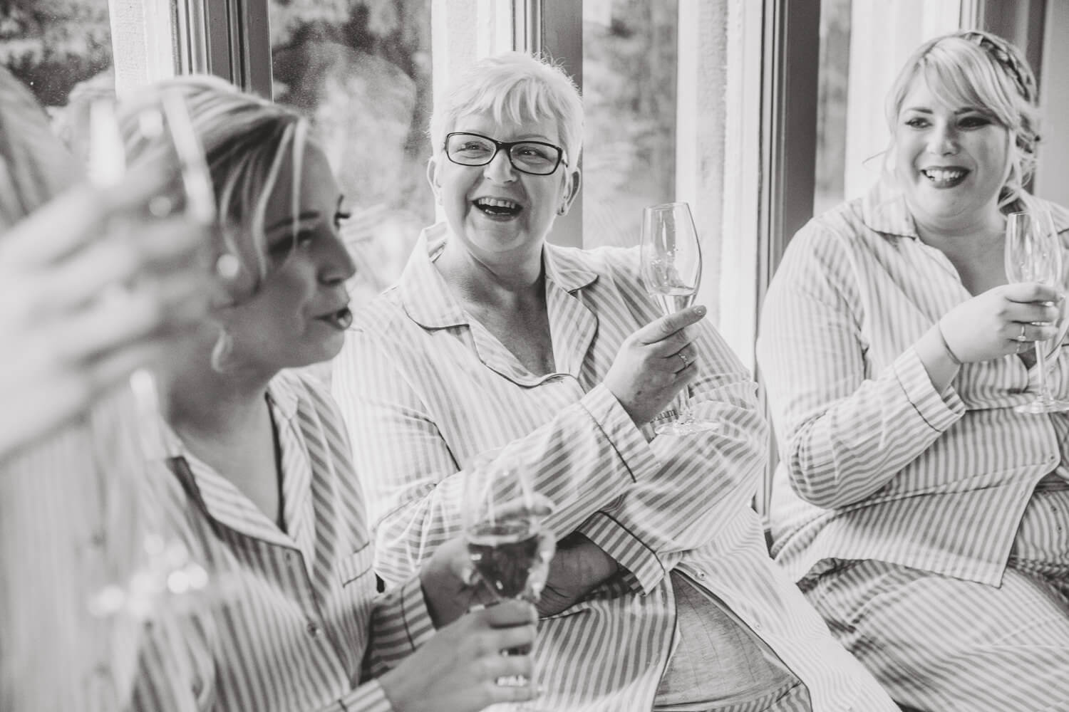 black and white photograph of mother receiving present from bride