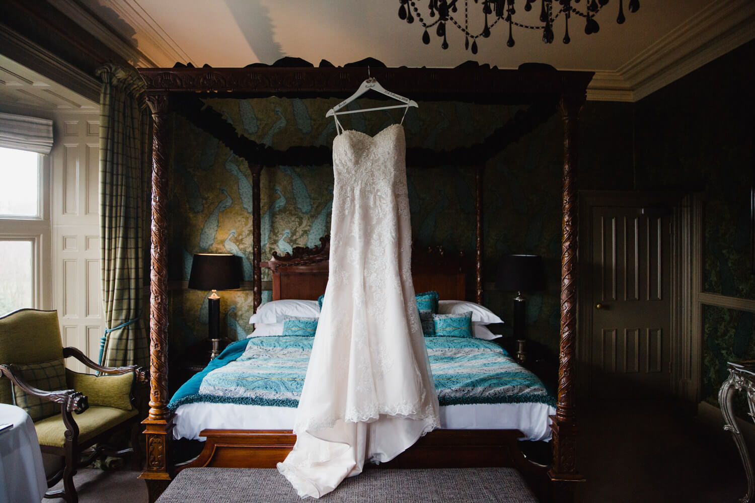 wedding gown hung up on four-poster bed