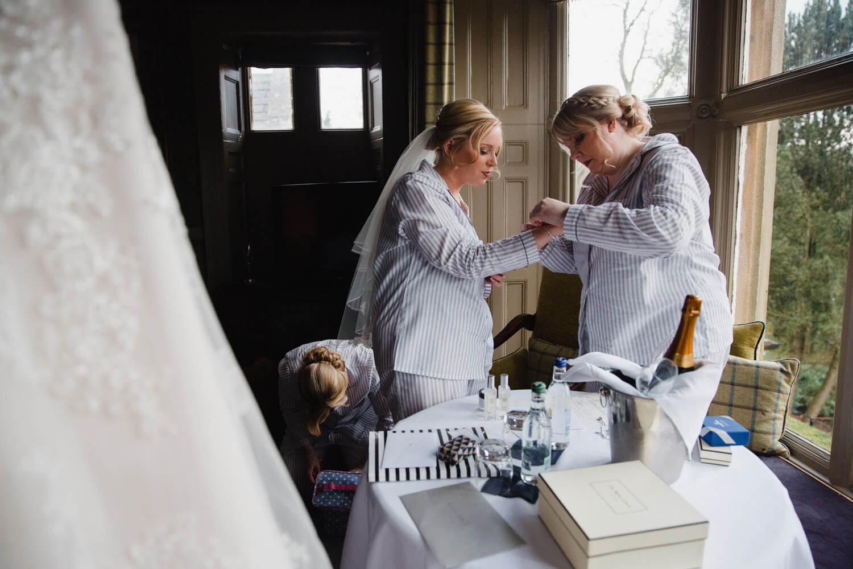 bridesmaid helping bride with jewellery before wedding ceremony