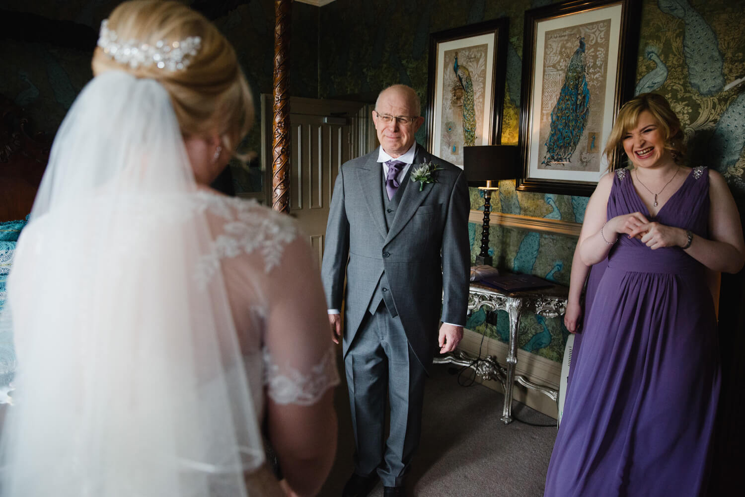 father of bride greets daughter in bridal suite for intimate moment before wedding nuptials