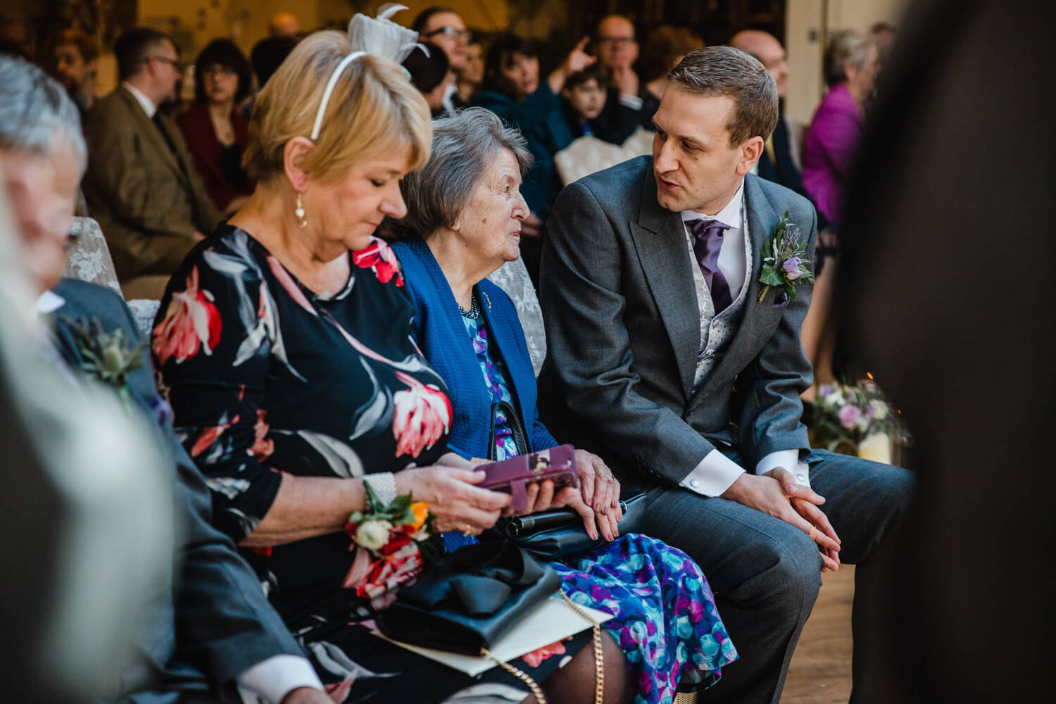 Groom with mother sat on top of aisle at Mitton Hall