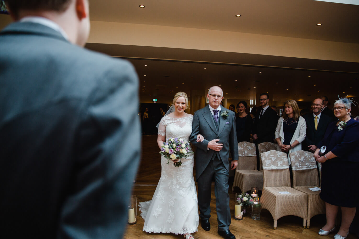 bride and father linking arms while smiling at groom in foreground