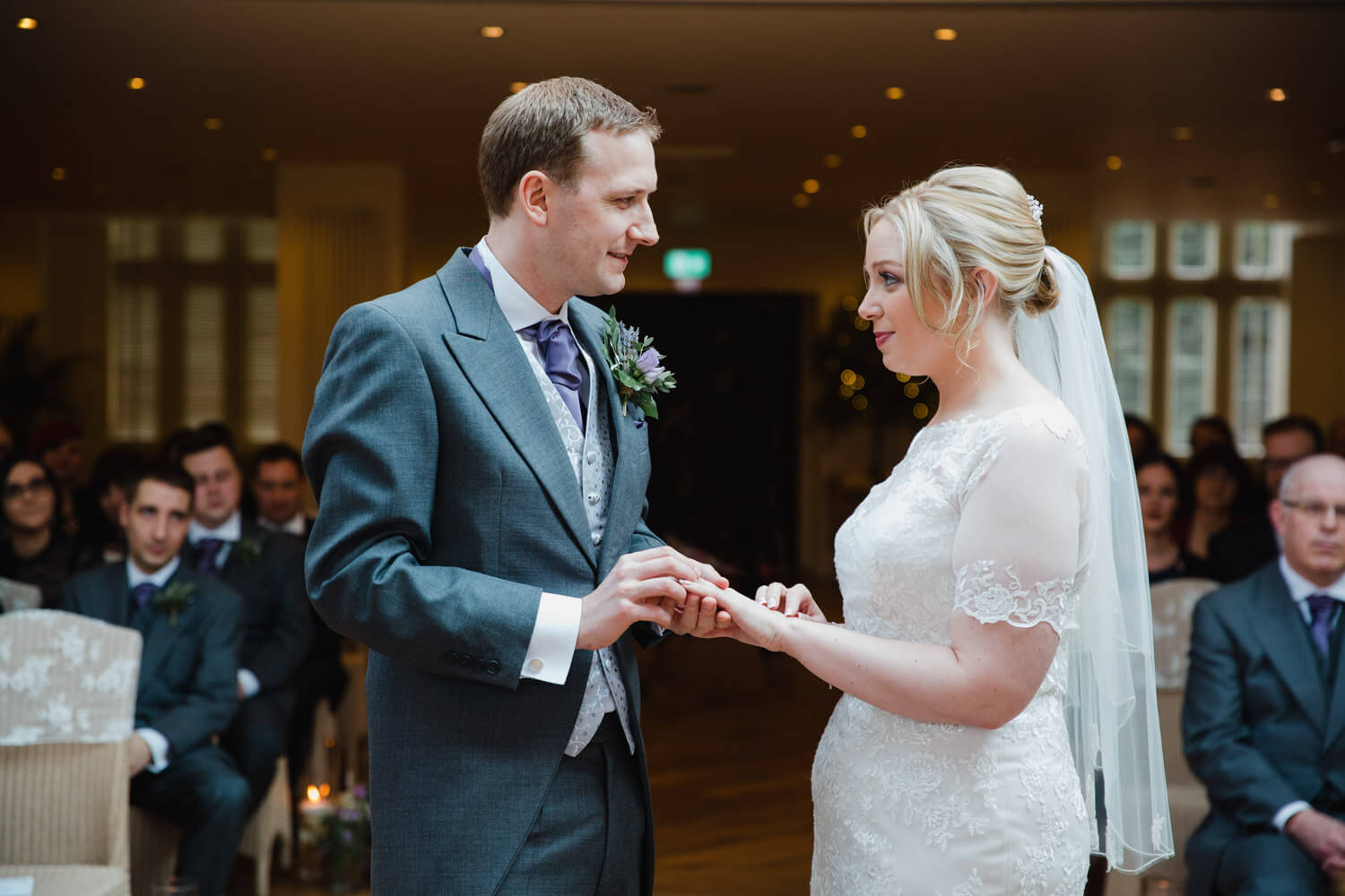 wedded couple exchanging wedding rings during service at Mitton Hall