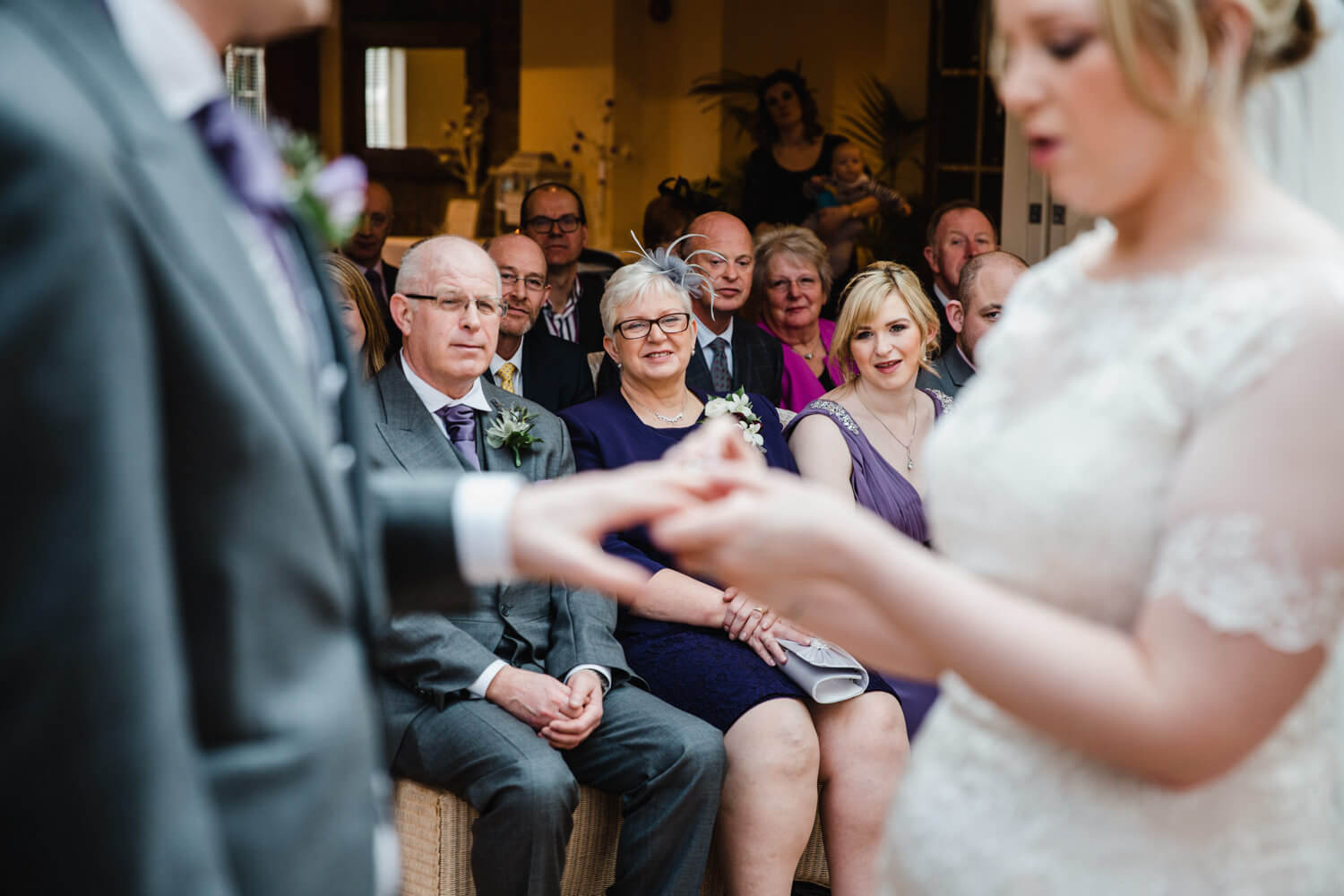 Mother of Bride smiling while newlyweds exchange rings at Mitton Hall