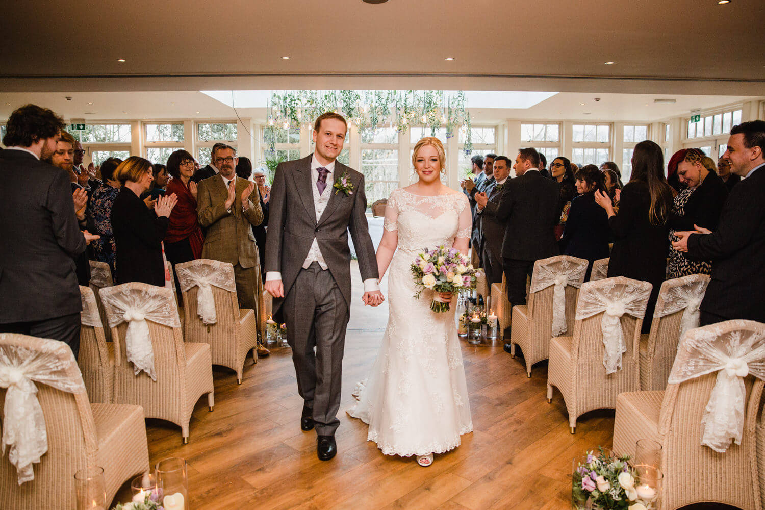 wide angle lens photograph of bride and groom holding hands after nuptials
