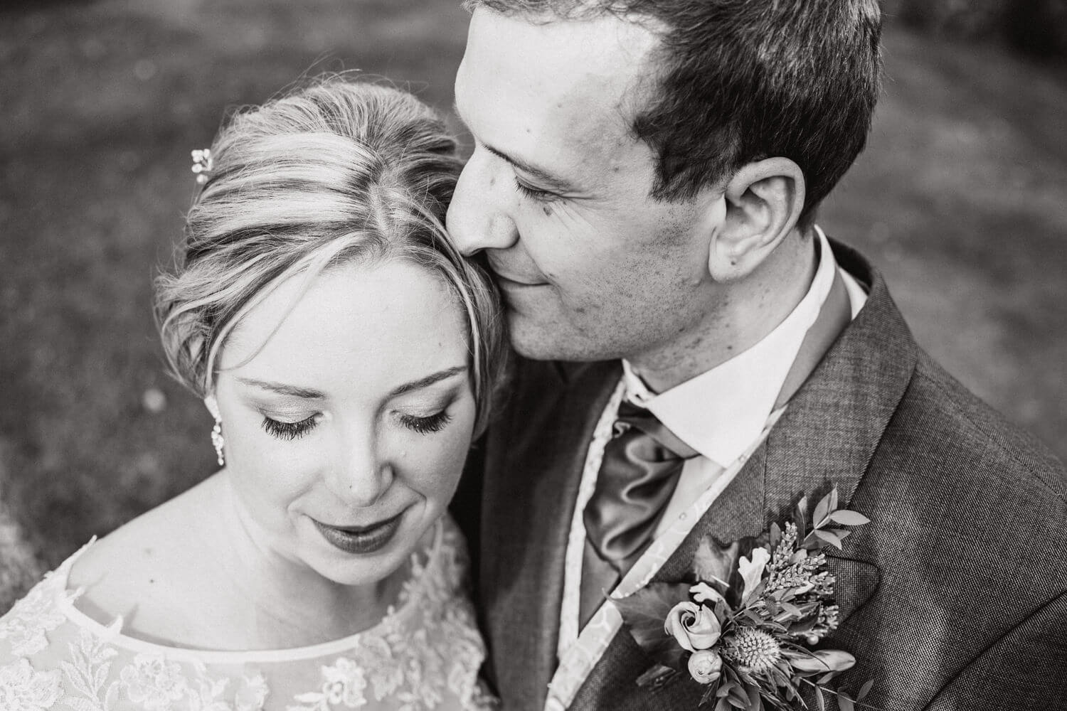 black and white portrait of bride and groom sharing intimate moment in grounds at Mitton Hall