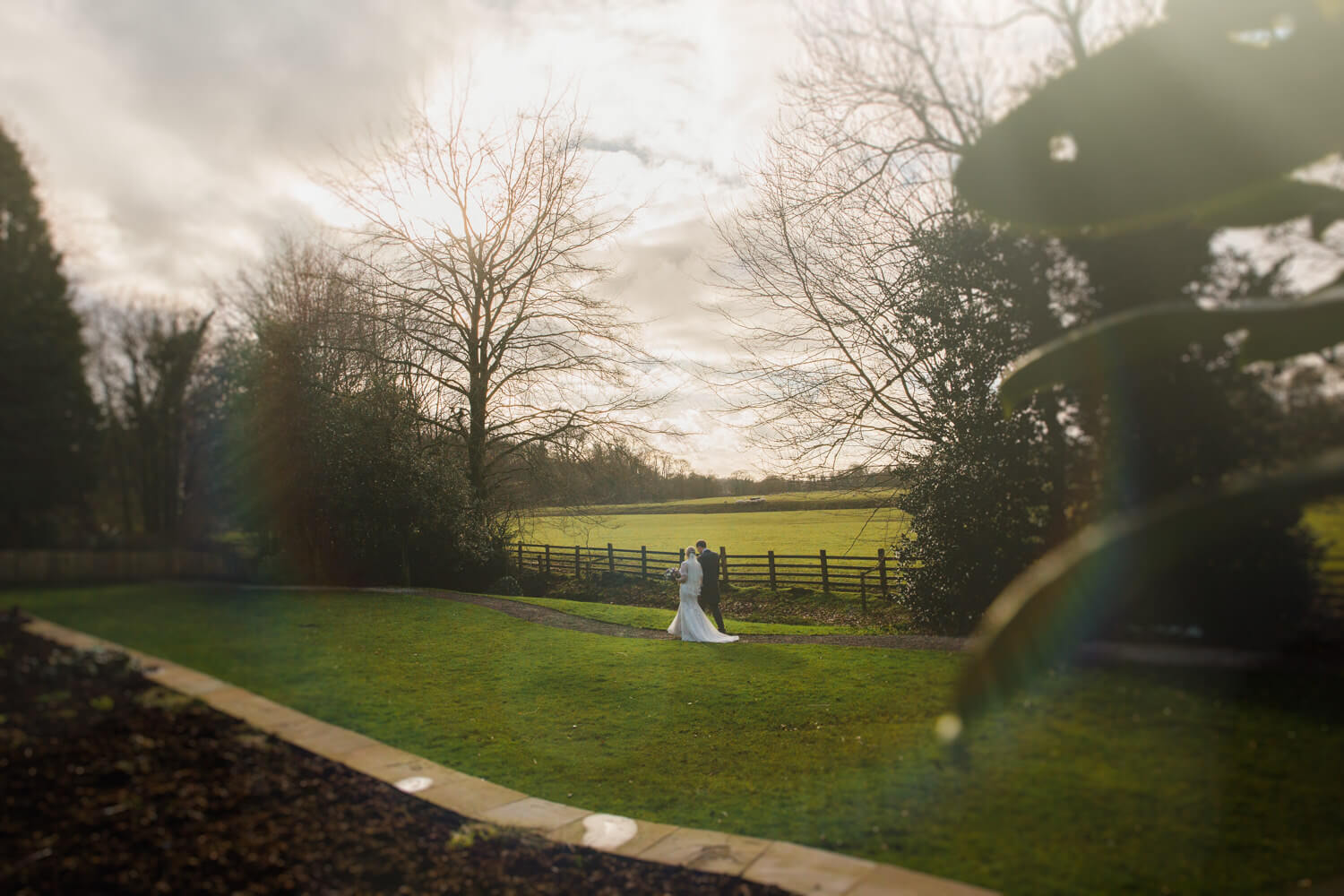 sun flare on lens portrait of newlyweds in gardens at Mitton Hall
