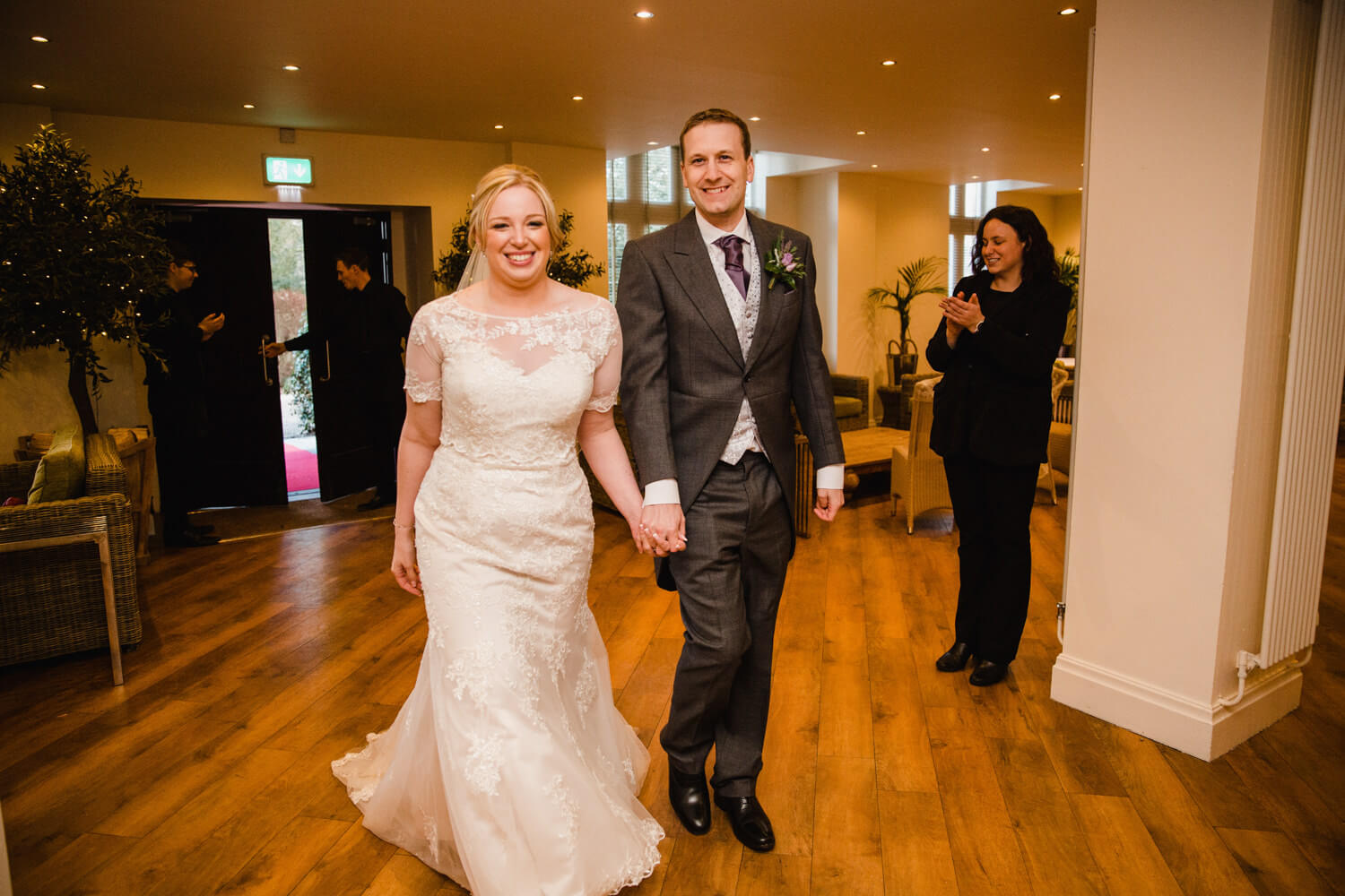 newly wedded couple enter reception venue for first dance