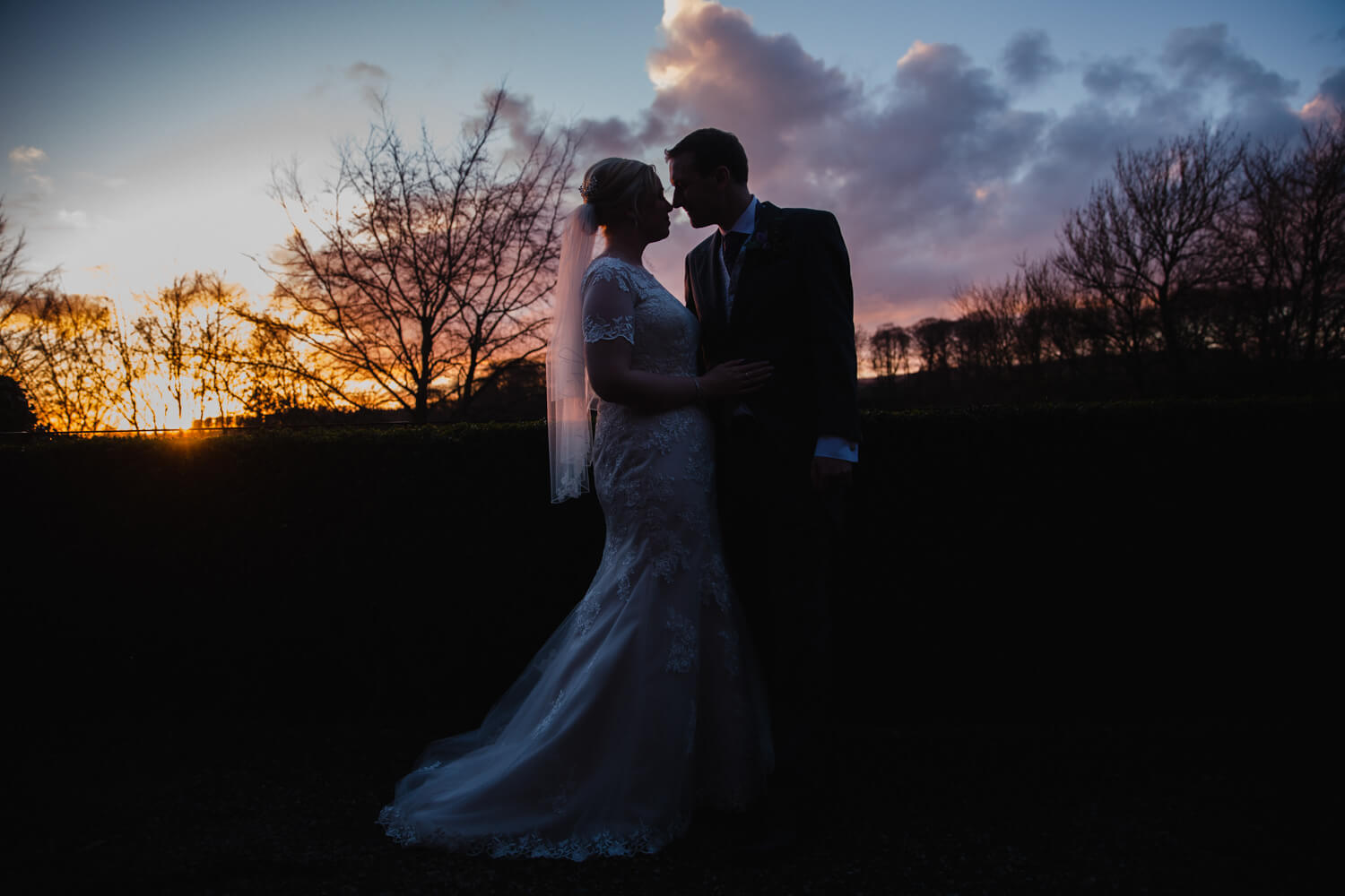 low light exposure silhouette portrait of newly married couple in sunset backdrop