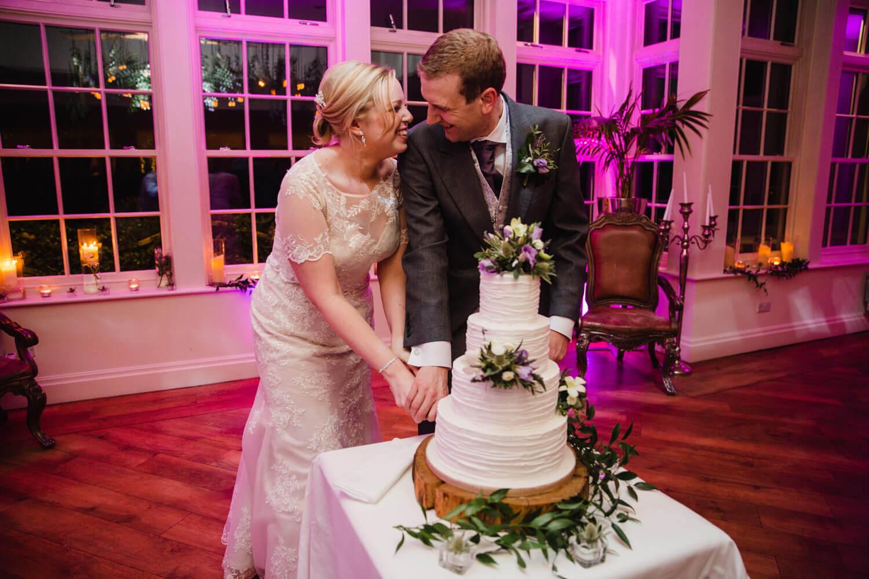 newlyweds cutting wedding cake together at Mitton Hall