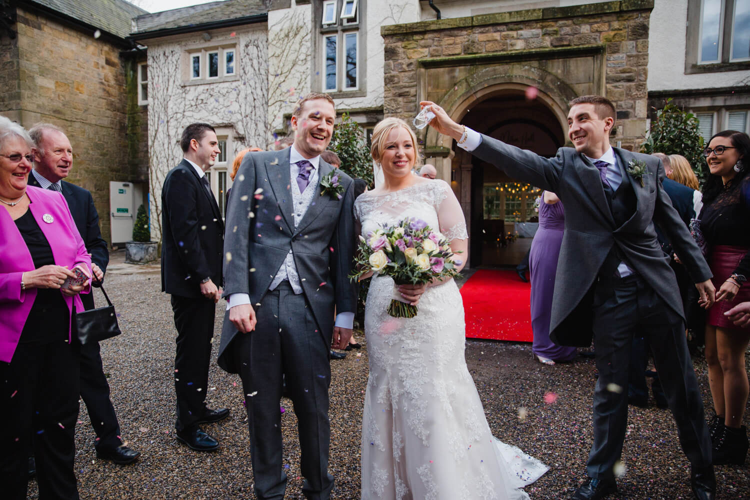 groomsman throwing confetti over newlywed couple outside Mitton Hall
