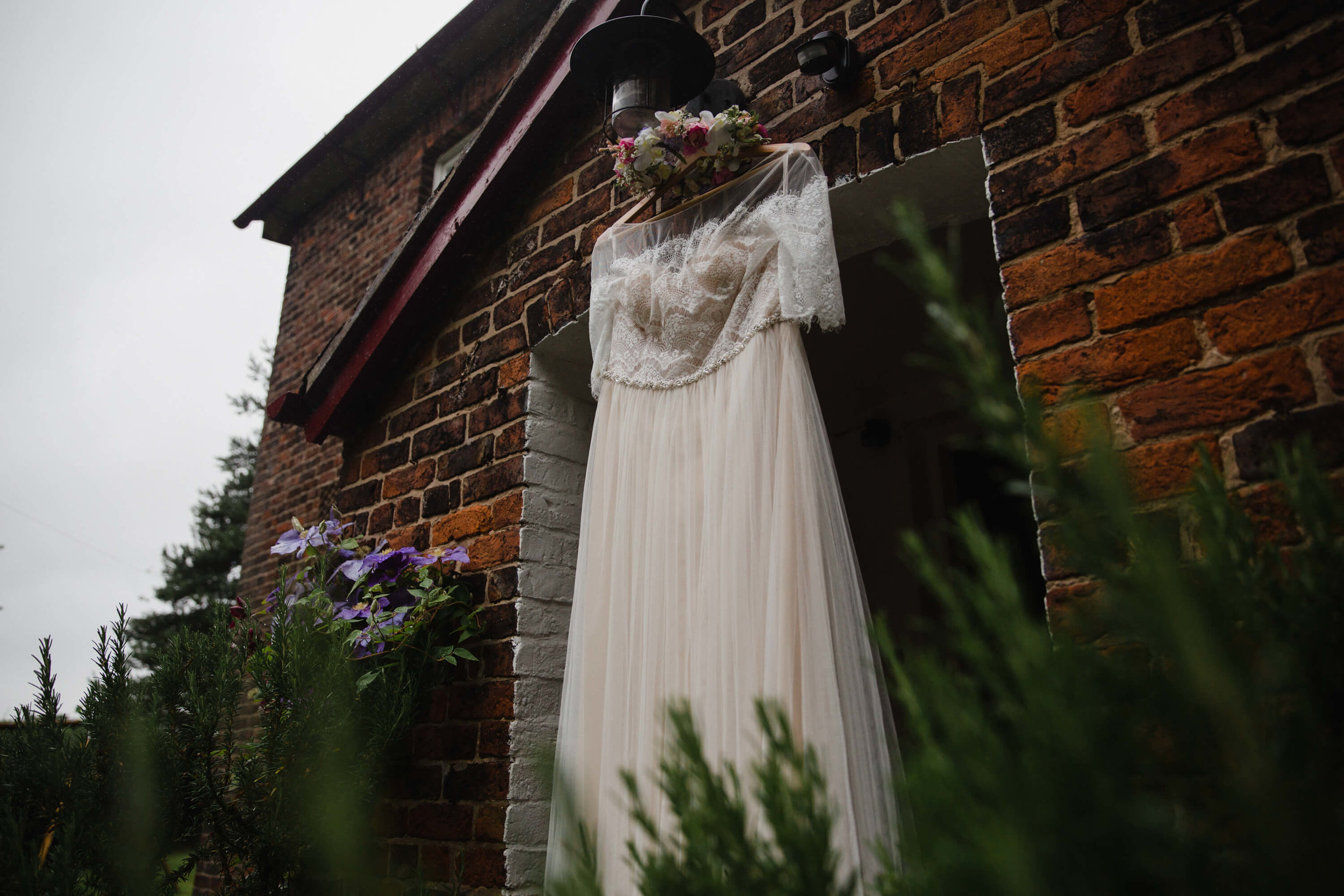 wide angle lens photograph of wedding gown hung in doorway with floral wreath head dress