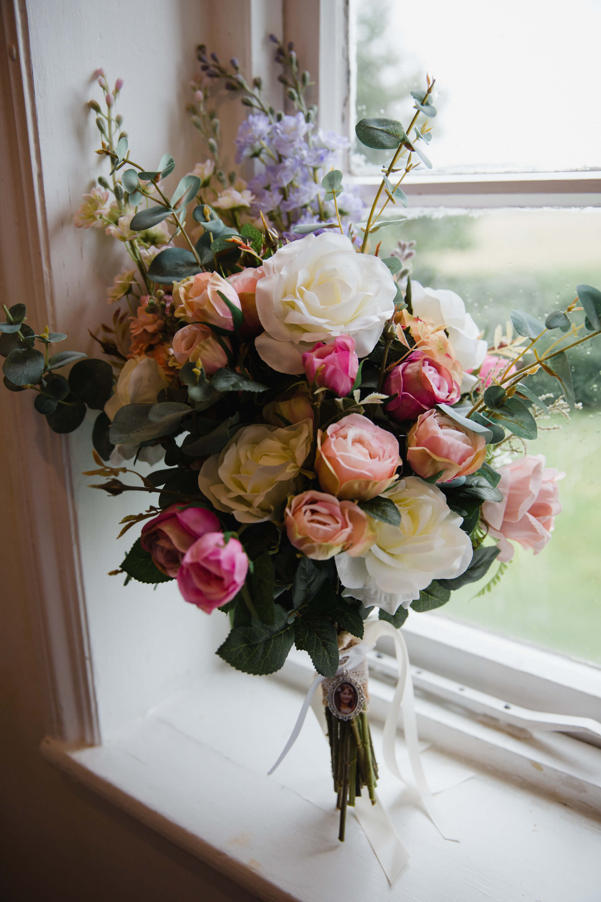 bouquet of flowers resting upright in window as natural light shines in