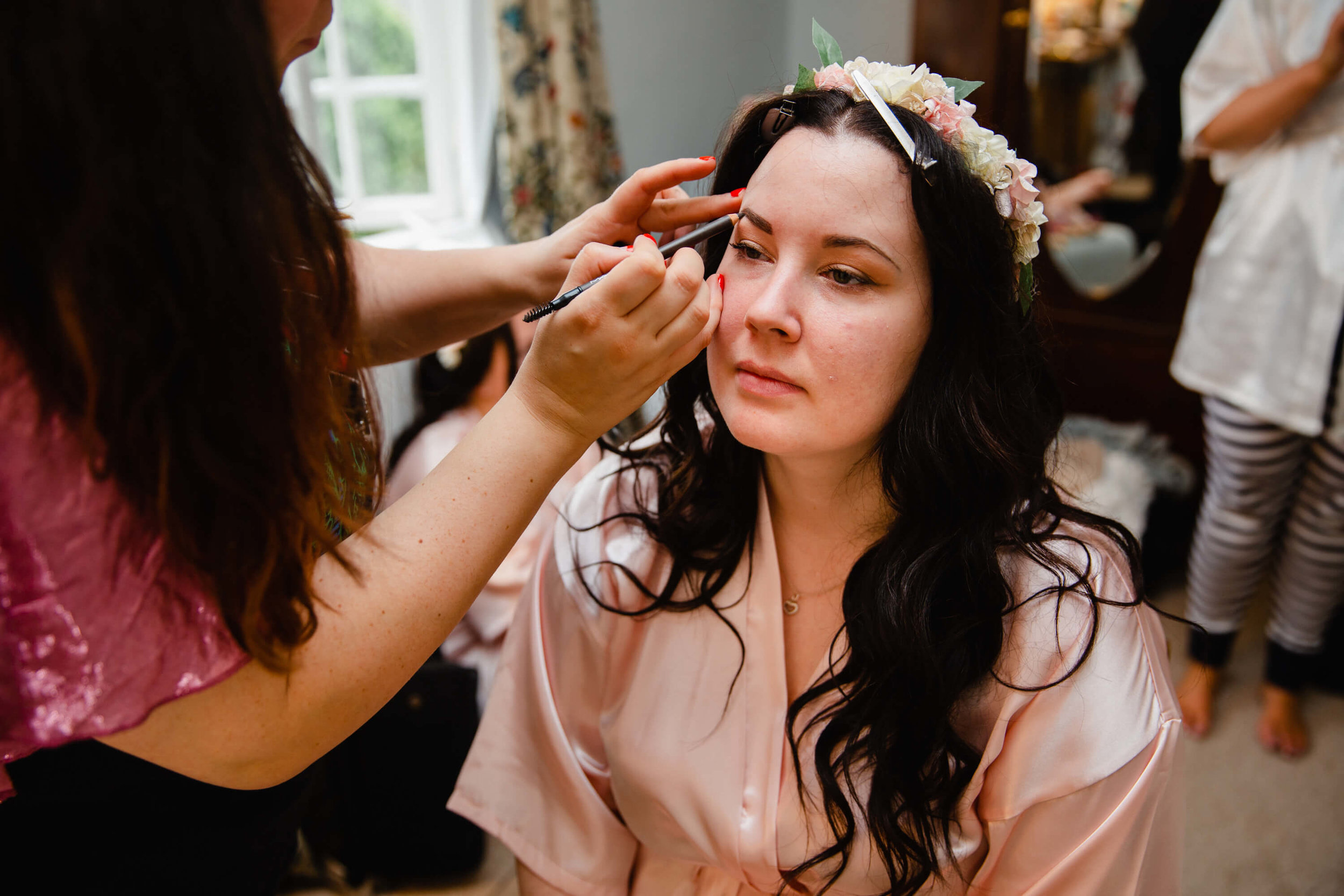 bridesmaid having make up applied before ceremony at Stock Farm
