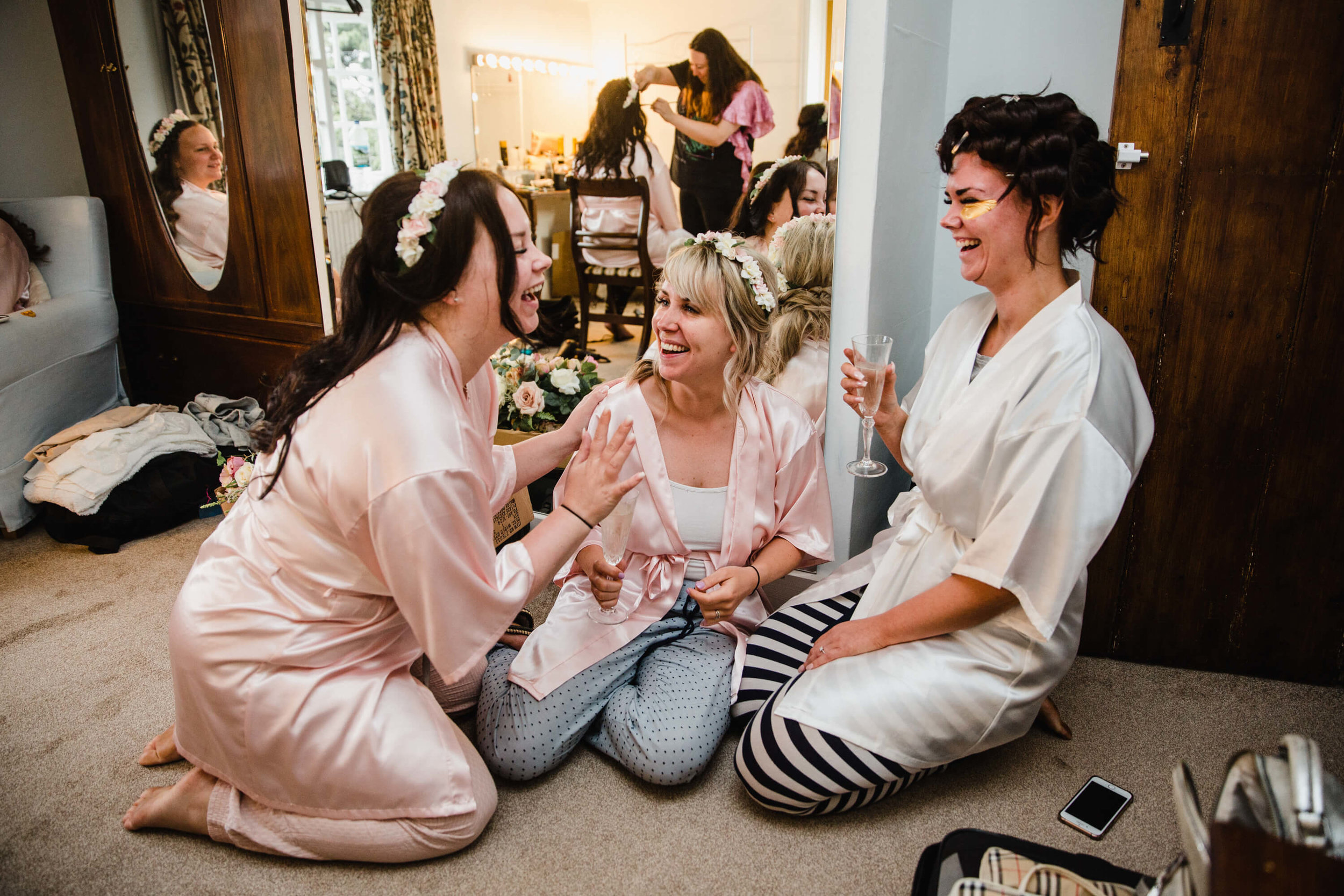 bridesmaids sharing laugh and joke with bride in mirror of bridal suite