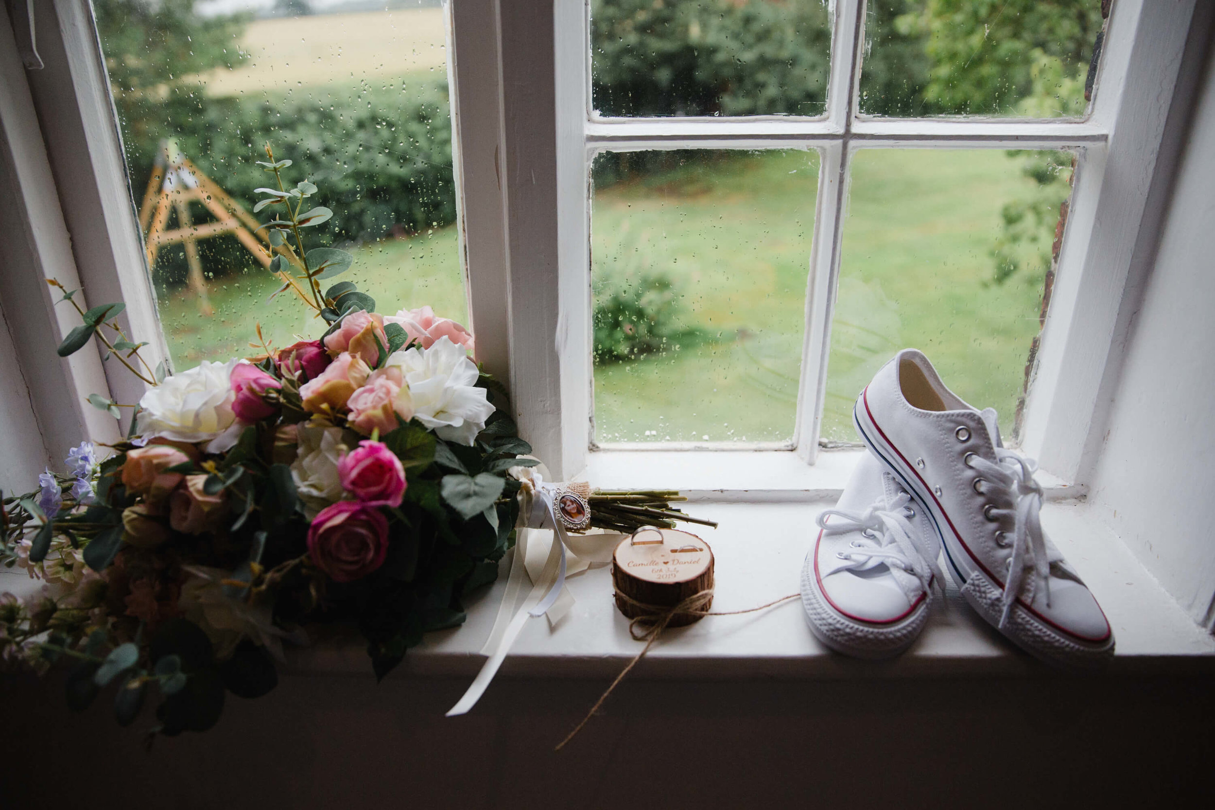 bouquet and converse wedding shoes sitting on window ledge overlooking garden at stock farm